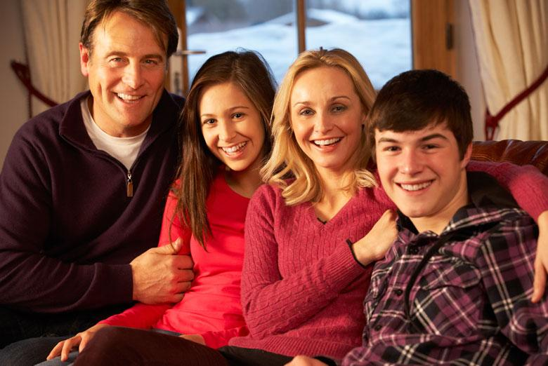 Older couple with older children sitting on their living room couch smiling