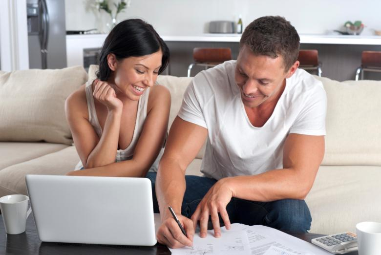Young Couple reviewing their financial plan while sitting on a couch in their living room.