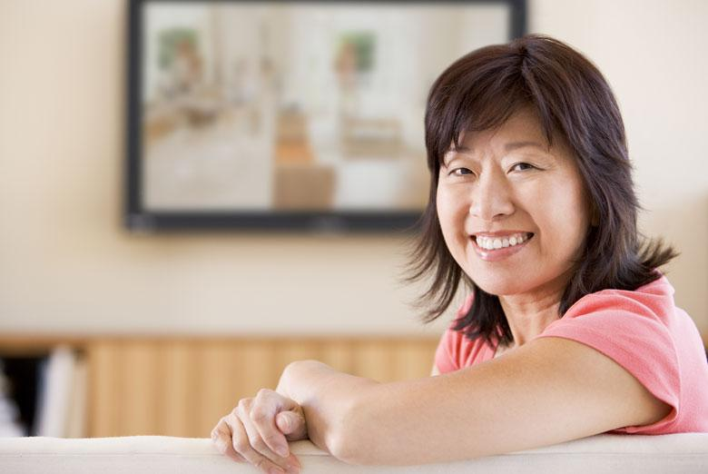 Older women sitting on her couch smiling
