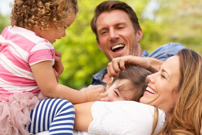 Family with young children lying on the grass playing and smiling
